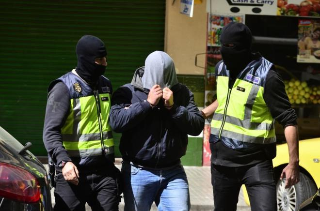 El detenido sale del domicilio acompañado por la Policía Nacional.
