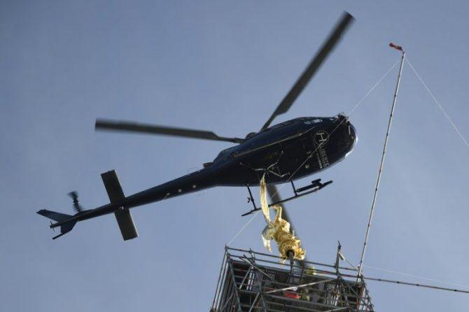 Un helicóptero traslada la estatua del arcángel del Monte Saint Michel a lo alto de la abadía.