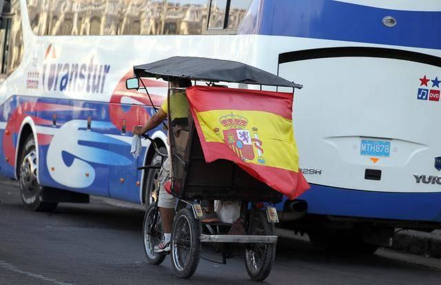 Un bicitaxi circula con una bandera de España en Cuba