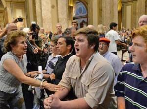 Una mujer pretende hacer callar a los que intentaban apagar con sus rezos la celebración de una liturgia dirigida por judíos en la catedral de Buenos Aires