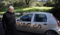 """El abad ortodoxo griego del Monasterio de la Santa Cruz en Jerusalén, el archimandrita Claudio, mira un coche rociado con un graffitti anti-cristianos que dice. """"precio"""" y con los neumáticos desinflados a las afueras de su monasterio."""