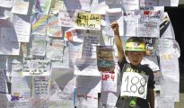 Un niño posa delante de una pared cubierta con mensajes de activistas tibetanos con motivo de la conmemoración, el pasado 17 de mayo, del 21 aniversario del secuestro de un niño tibetano de siete años , considerado como la reencarnación del Panchen Lama, en Dharamshala, India.