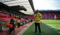 Un empleado permanece sobre el césped del estadio de Old Trafford mientras el público abandona las gradas, el domingo 15 de mayo en la ciudad inglesa de Manchester