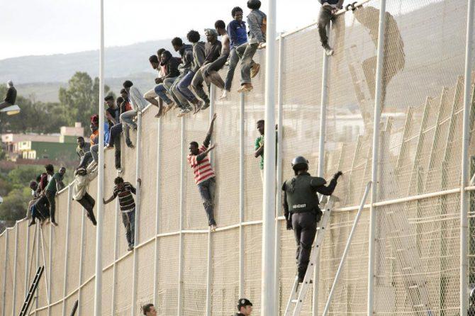 Ilegales encaramados a la valla en Melilla.