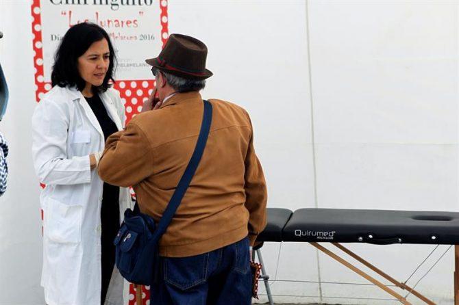 Una médico atiende a una de las personas que ha acudido hoy a la carpa que la división de Cáncer de Piel y Melanoma España, integrada en el Grupo Español de Pacientes con Cáncer (Gepac), ha instalado en la Plaza de Santa Isabel II de Madrid.