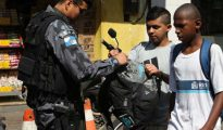 Un policía registra las mochilas de dos jóvenes en Rio.