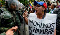 """Una mujer exhibe un cartel que seña """"Morimos de hambre"""" durante una protesta contra el estado de emergencia decretado por el presidente Nicolás Maduro, el 18 de mayo de 2016 en Caracas"""