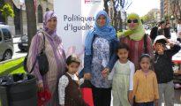 """Musulmanas con sus hijos junto a un cartel del Ayuntamiento de Tarragona en favor de las """"polítiques d'igualtat"""""""