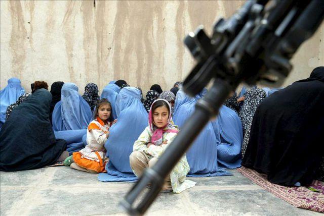 Dos niñas afganas rodeadas de mujeres con burka.