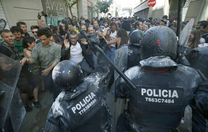 Manifestantes y antidisturbios de los Mossos d'Esquadra, durante los incidentes producidos el domingo en el barrio de Gràcia de Barcelona.