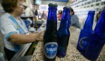 Una mujer vende cerveza Polar en un bar de Caracas.