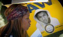 Una joven sostiene un cartel con la imagen del adolescente negro Trayvon Martin durante una marcha para conmemorar el 50º aniversario de la Marcha sobre Washington de Martin Luther King Jr.