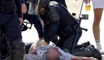 Un policía atiende a un aficionado tras una pelea por las calles de Marsella.
