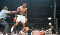 En esta imagen de archivo del 25 de mayo de 1965, el campeón de peso completo Muhammad Ali es retenido por el árbitro Joe Walcott, a la izquierda, después de que Ali noqueara a su rival Sonny Liston en el primer asalto de su combate por el título en Lewiston, Maine.