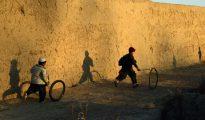 Un niño afgano juega con un neumático.