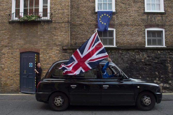 Un taxista londinense ondea una bandera británica mientras circula por una calle donde una bandera europea ondea en una ventana en Londres (Reino Unido) hoy, 24 de junio de 2016.
