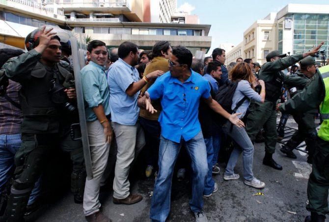 Manifestantes de la oposición son obligados a retirarse de los alrededores de la sede del Consejo Nacional Electoral por la Guardia Nacional Bolivariana en Caracas, el jueves 9 de junio de 2016.