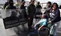 Policías Bolivianos desalojan a una docena de personas con discapacidad, en sillas de ruedas y con muletas luego de que protestaran frente a las puertas de la clínica donde operaron de una rodilla al presidente boliviano, Evo Morales, y que estuvo custodiada por decenas de policías.