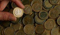 Una persona enseña una moneda de euro.