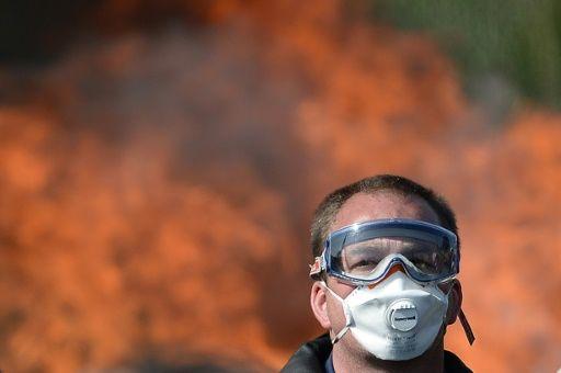 Un hombre con mascarilla en una protesta de trabajadores en huelga que la policía antidisturbios acudió a disolver mientras bloqueaban el acceso a una gasolinera en Donges, oeste de Francia, el 27 de mayo de 2016.