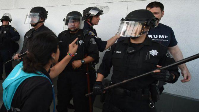 Una mujer grita a un seguidor de Trump mientras la policía los separa.