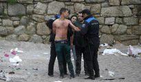 Agentes de la Policía Local de A Coruña arrestan al joven que se bañaba en la playa del Orzán, la más peligrosa de la bahía coruñesa, sin hacer caso de las advertencias de la Policía Local.