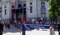 """Imagen de algunos manifestantes junto la pancarta con el lema: """"Orgullosos de nuestra historia"""". Al fondo, colgada en el Ayuntamiento, la bandera del arcoiris gay."""