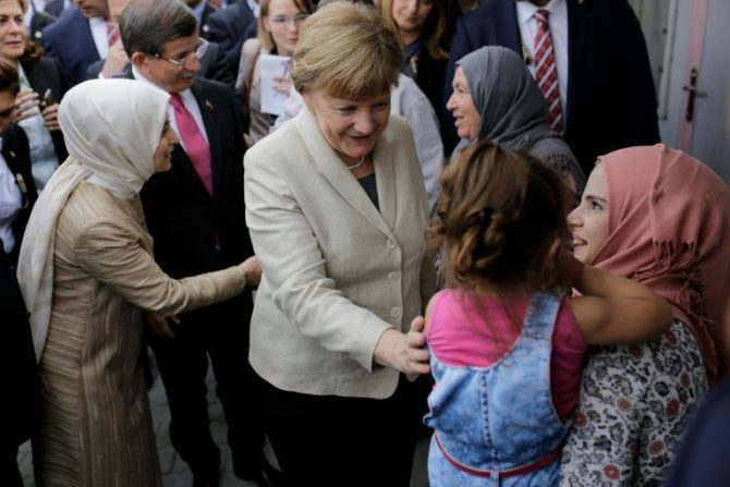 La canciller alemana Angela Merkel (c) y el primer ministro turco Ahmet Davutoglu (atrás)hablan con refugiados el 23 de abril de 2016 en Gaziantep.