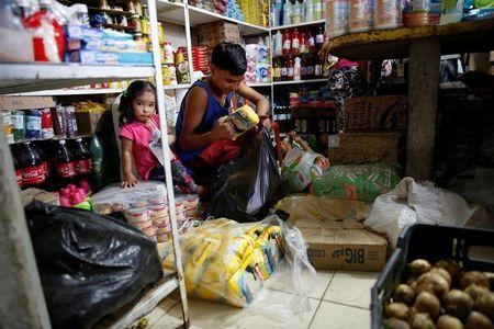 En la imagen, un niño mete paquetes de harina de maíz colombiana en una bolsa de plástico, en un mercado en La Fria, Venezuela.