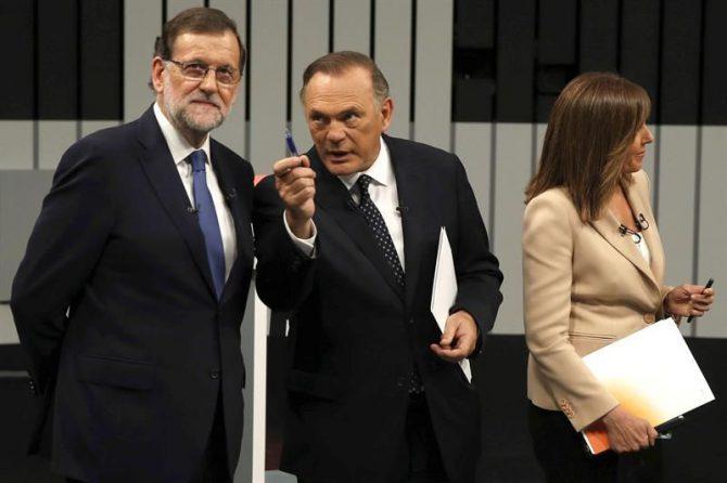 El presidente del Gobierno en funciones y del PP, Mariano Rajoy (i), atiende a uno de los moderadores del programa, Pedro Piqueras (c), junto a otra de las presentadoras Ana Blanco (d), momentos antes de iniciar el único debate a cuatro de la campaña electoral.
