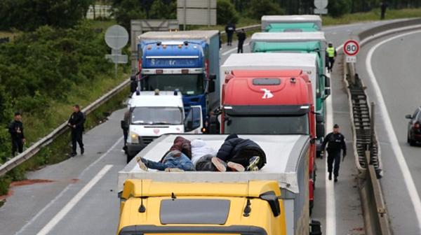 Inmigrantes del campo de Calais intentan llegar a Reino Unido en el techo de un camión.