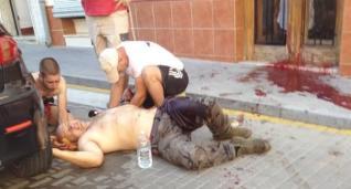 Un amigo de la víctima intenta taponar la herida de bala recibida en el brazo.