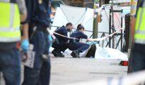 Dos agentes de Policía observsan uno de los cadáveres.