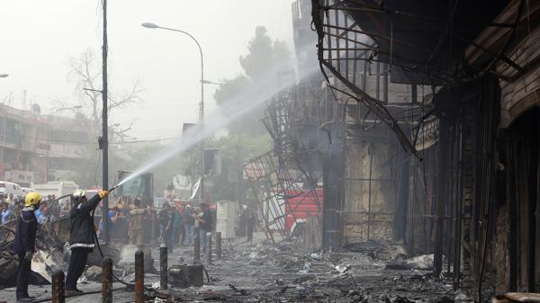 Un grupo de bomberos trata de extinguir las últimas llamas del edificio que quedó carbonizado.
