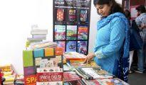 Una mujer observa varias publicaciones en castellano en las celebraciones del Día del Español en la India en el Instituto Cervantes de Nueva Delhi.