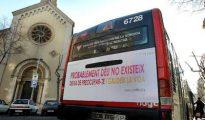 Un autobús con un letrero ateo y hedonista pasa junto a una iglesia en Barcelona.