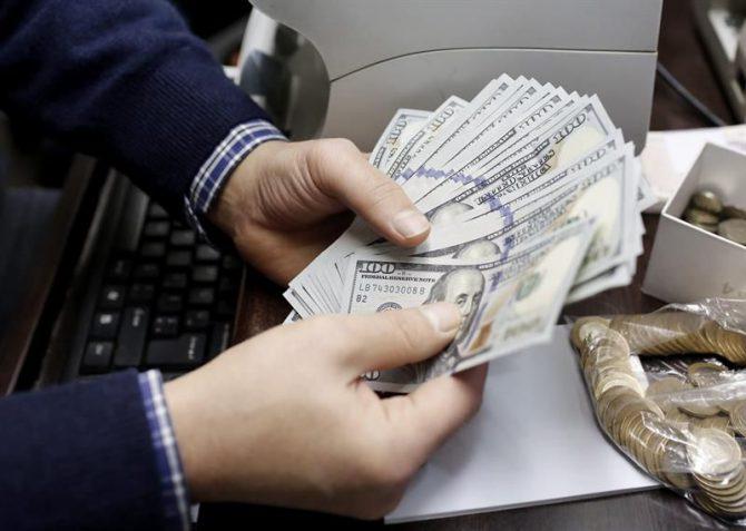 Un hombre cuenta billetes en una oficina de cambio de divisas.