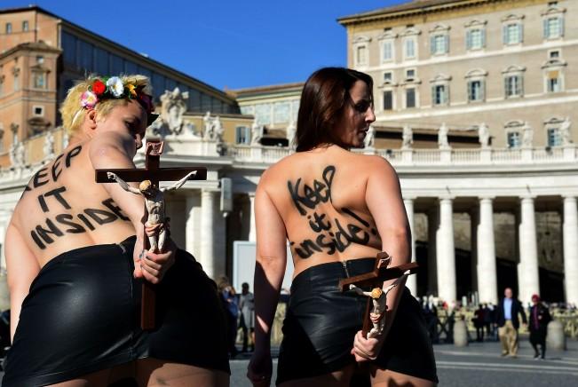 Feministas de Femen apoyan sendas cruces en sus traseros dentro del Vaticano.