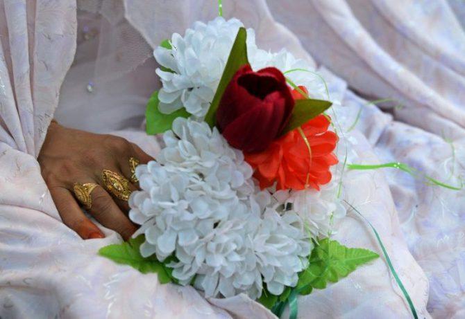 Una novia sostiene un ramo de flores durante un casamiento en Kabul