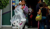 Una mujer sale de un supermercado tras comprar papel higiénico.