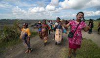 Sobrevivientes vestidos de mujer en apoyo a las mujeres que perdieron sus medios de vida en un alud, participan en un desfile en la isla de Java el 29 de mayo de 2016