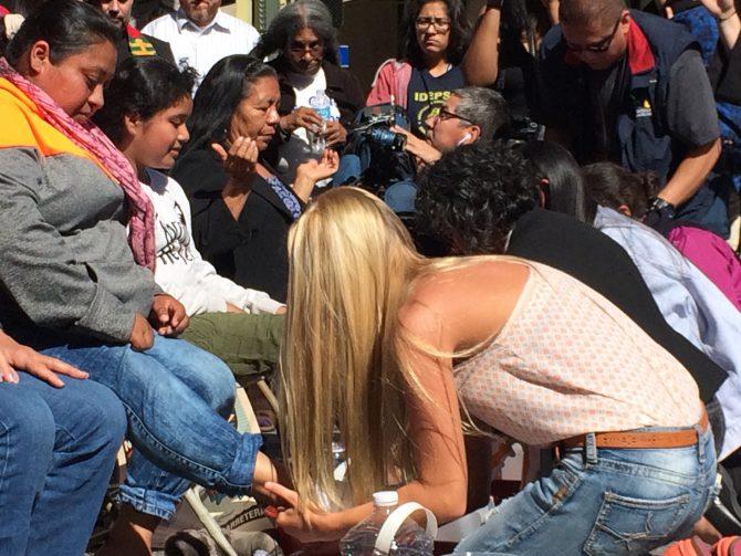 Una joven estadounidense lava los pies a inmigrantes centroamericanos en proceso de deportación.
