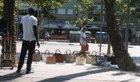 Un 'mantero' vende bolsos en el paseo Joan de Borbó.