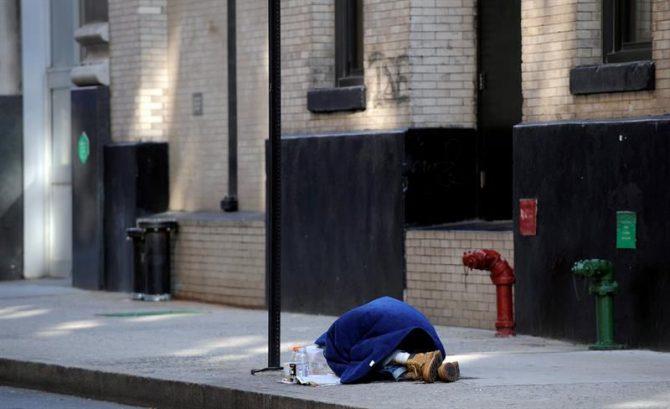 Un mendigo duerme en una calle de Nueva York, EE.UU.