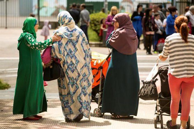Mujeres ataviadas con velo esperan a sus hijos en la puerta de un colegio.