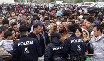 Agentes de policía dan instrucciones a los refugiados que esperan en la frontera con Hungría,