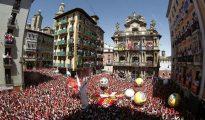 """Miles de personas festejan con sus pañuelos alzados el inicio de las fiestas de San Fermín 2016 tras el lanzamiento del tradicional chupinazo"""" desde el balcón del Ayuntamiento de Pamplona."""