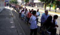 """Cientos de personas aguardan en una calle antes de cruzar por el puente fronterizo """"Simón Bolívar"""" entre Colombia y Venezuela, en la ciudad de San Antonio del Táchira (Venezuela)."""