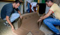 Unos hombre pliegan un ataúd de cartón en la localidad venezolana de Barquisimeto, el 9 de agosto de 2016. Ante el alto costo de los féretros, los venezolanos buscan materiales alternativos para su fabricación