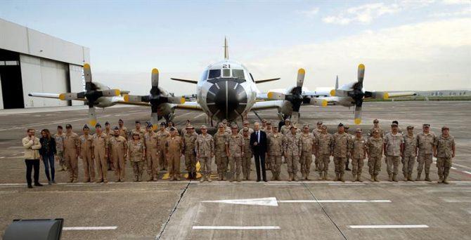 El ministro de Defensa, Pedro Morenés (c), durante una visita a las tropas españolas desplegadas en Sicilia, posa con parte de los efectivos españoles delante de un avión de vigilancia marítima.